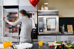 hombre hablando por teléfono abriendo la refrigeradora